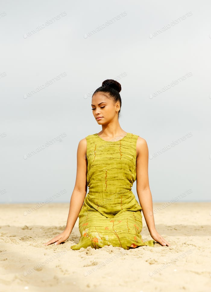 Beautiful young woman meditating at the beach