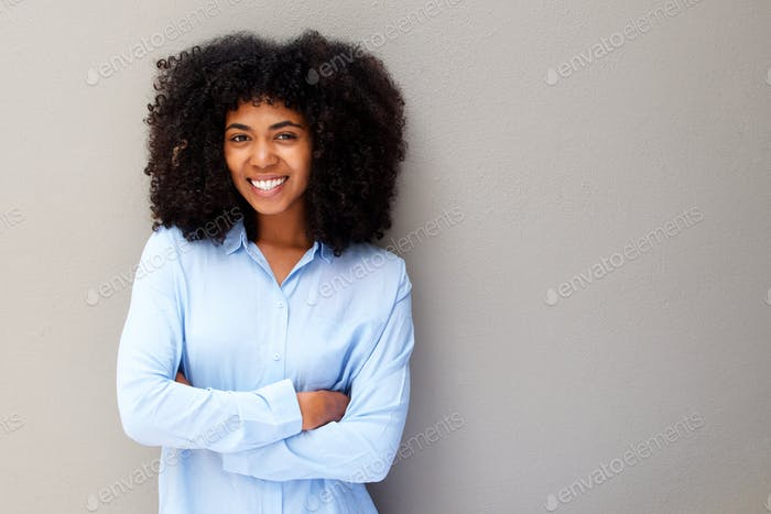 happy young african american woman smiling against gray background with arms crossed