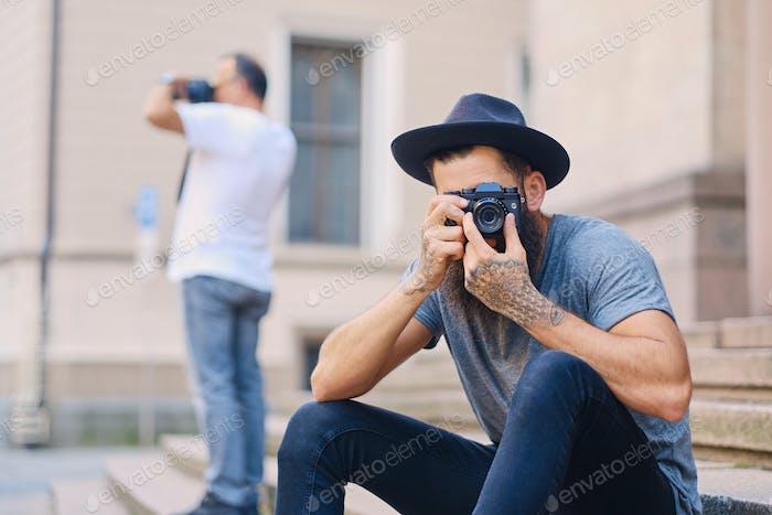 Уличный фотограф сидит на ступеньке.