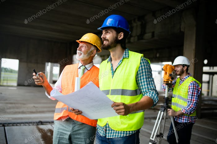 Engineer, foreman and worker discussing in building construction site