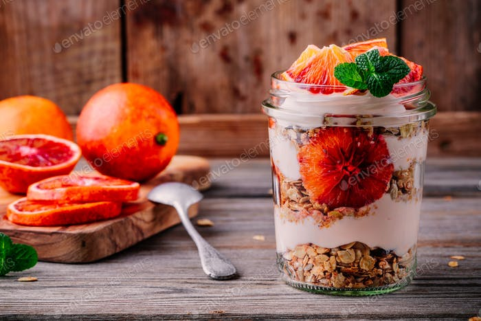 healthy breakfast  glass jar yogurt parfait with homemade granola and blood orange