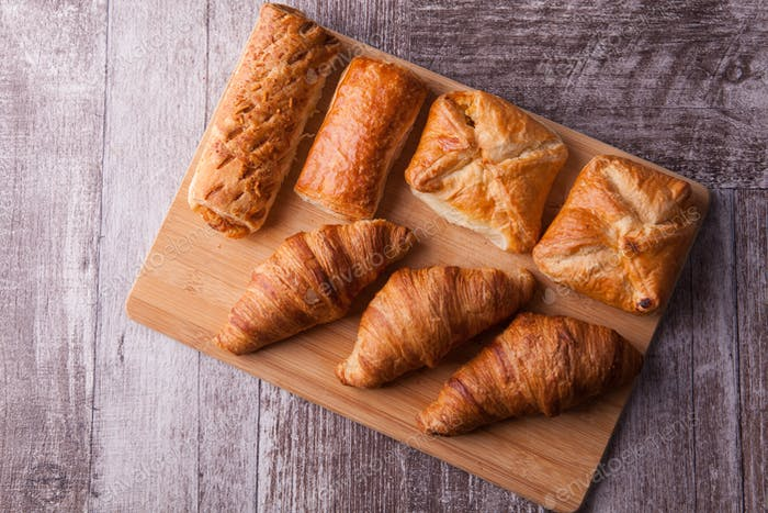 An assortment of freshly baked pastry aligned on cutting board