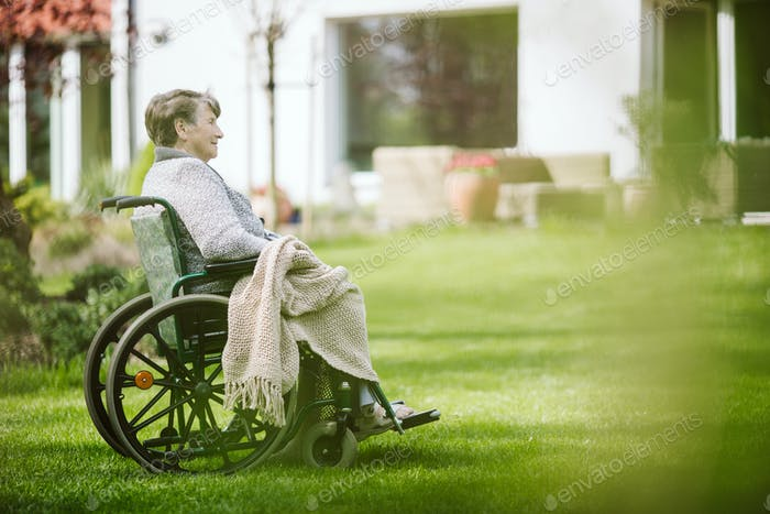 Grandmother on the wheelchair in the garden