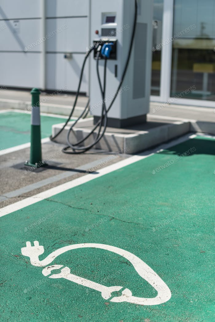 Electric charge station. Electric plug for charging cars. Car charging symbol painted on asphalt.