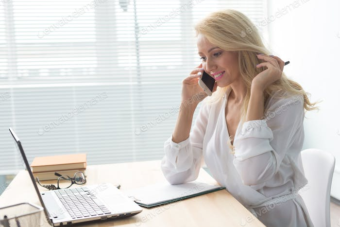 Business, technology and communication concept - blonde woman talking phone while watching laptop