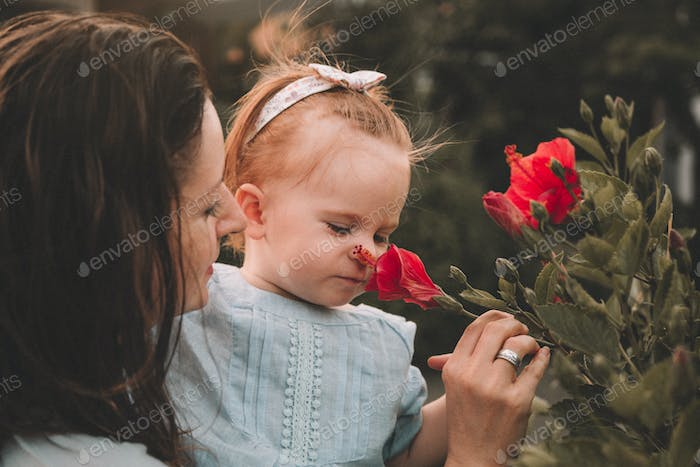 Cute little baby girl with her mother sniffing flowers in a garden in summer day