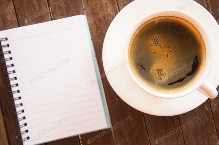 White coffee cup with notebook on wooden table.Copy space for te