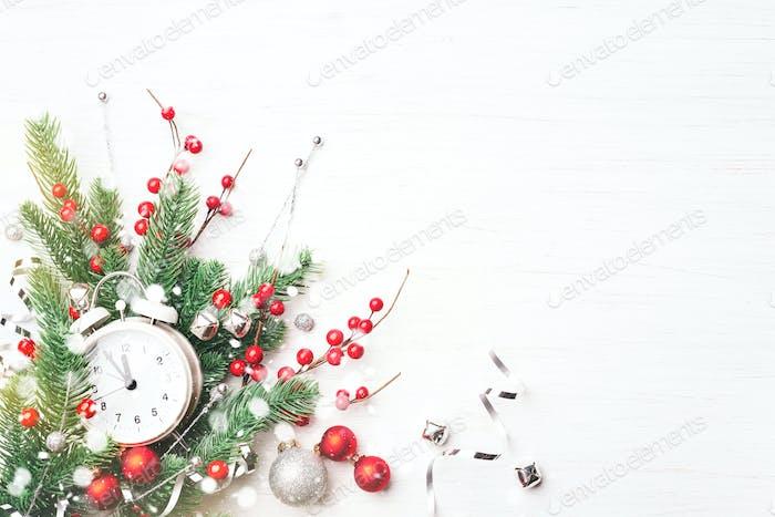 Weihnachtskomposition mit Uhr und Tannenzweigen.