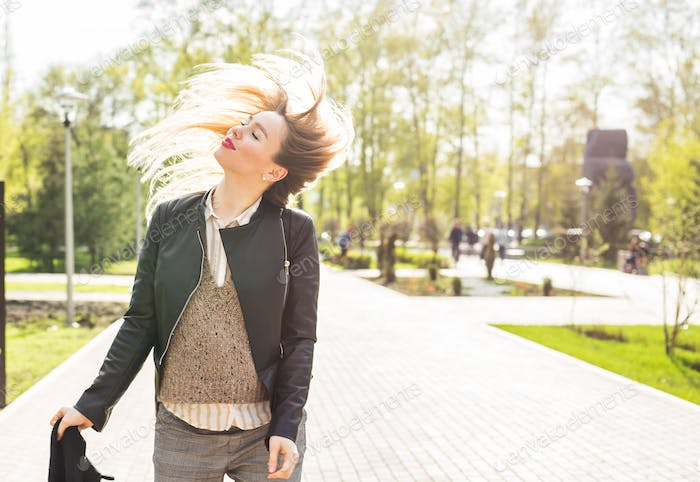 Trendy woman with flying hair outdoors