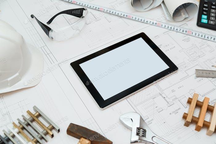 Baupläne mit Tablet, Zeichnungen und Werkzeugen.