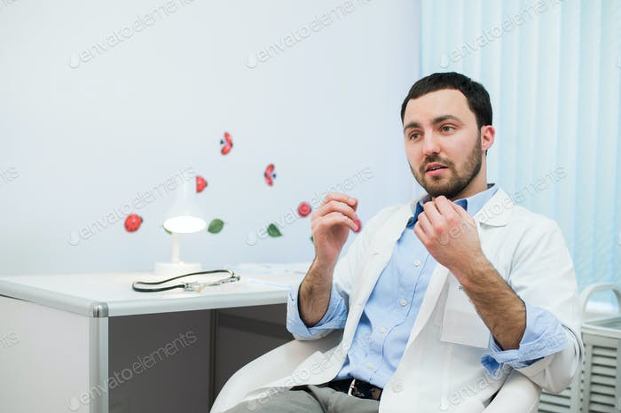 Friendly male medicine therapeutist doctor sitting in office, talking patient and looking to camera