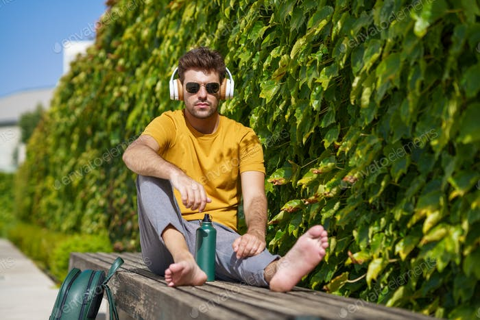 Male sitting outside using an aluminum water bottle, headphones and backpack
