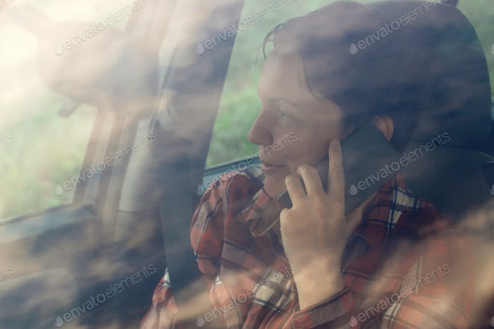 Smiling woman talking on mobile phone in car
