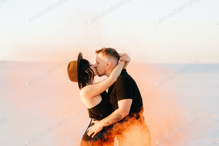 guy and a girl in black clothes hug and run on the white sand