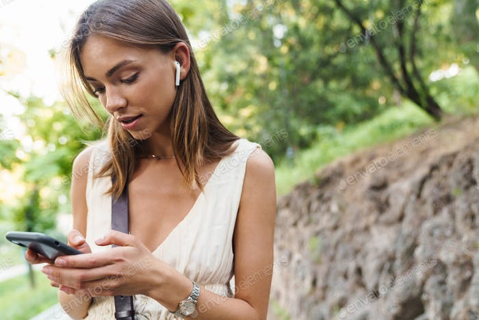 Image of young woman wearing earbuds holding cellphone in park