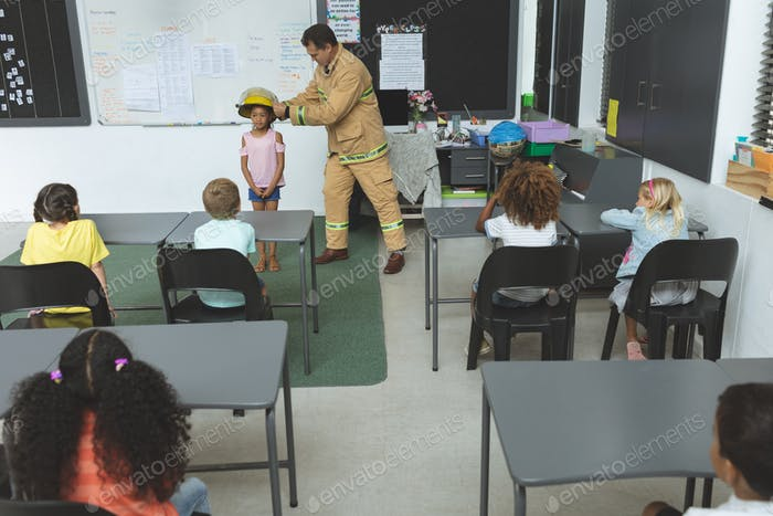 Overhead view of firefighter teaching student about fire safety in classroom at school