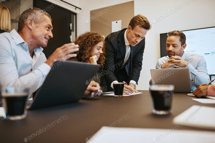 Diverse business colleagues talking together in an office boardroom