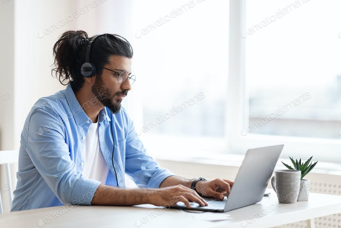 Handsome western freelancer guy working remotely with laptop at home office