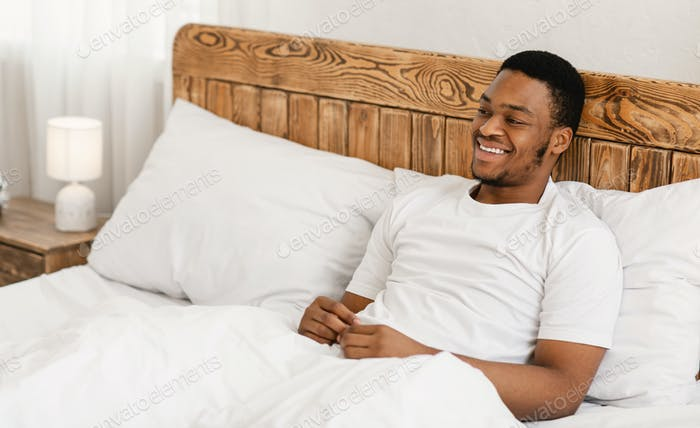 Happy Relaxed African American Man Sitting In Bed In Bedroom
