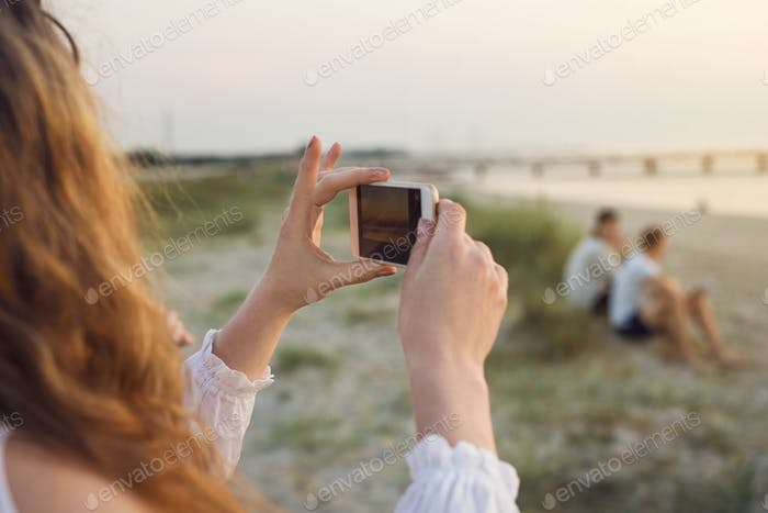 Young woman taking photo on beach