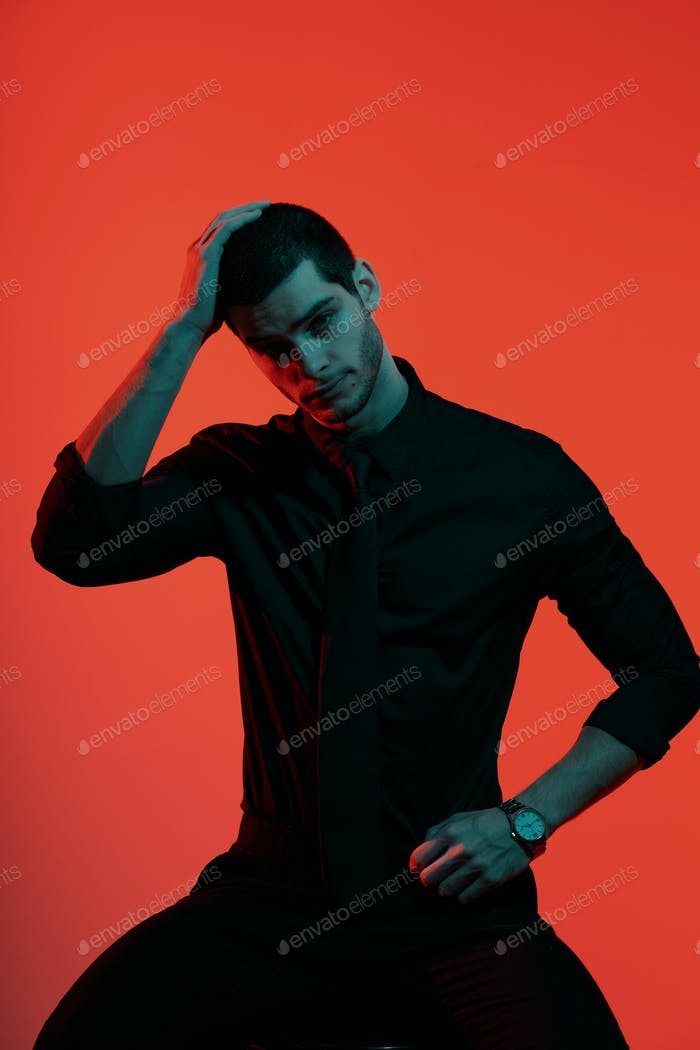Portrait of a young confident handsome businessman in blue and red light