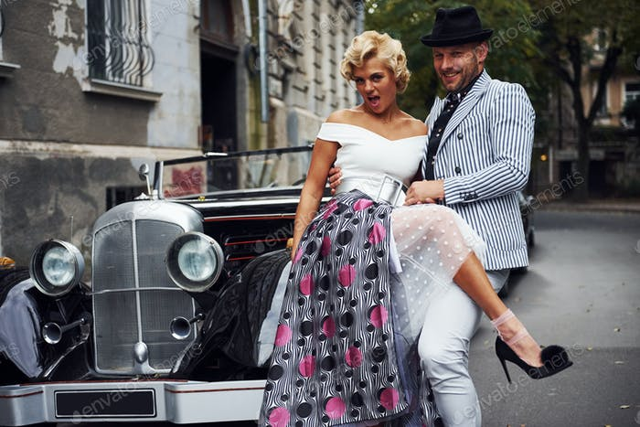 Beautiful couple in old fashioned wear is in city with retro car