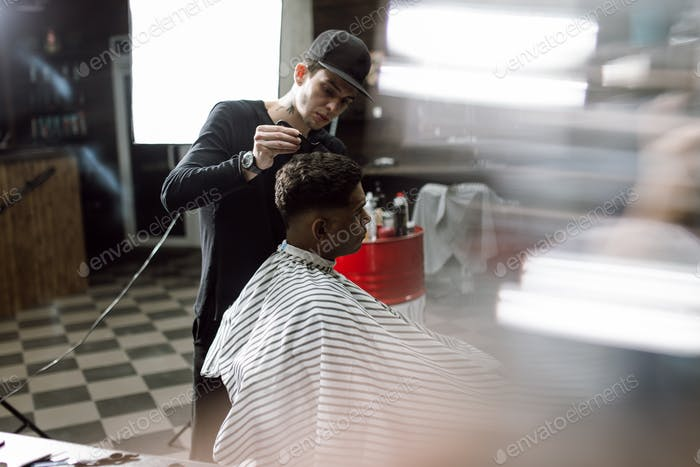 The fashion barber in black clothes makes a razor cut hair for a black-haired man sitting in the