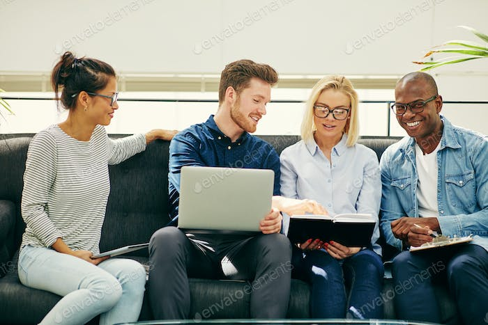 Smiling group of businesspeople talking together on an office sofa
