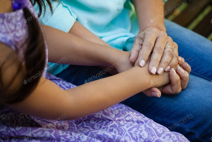 Midsection of senior woman holding hands of grandmother