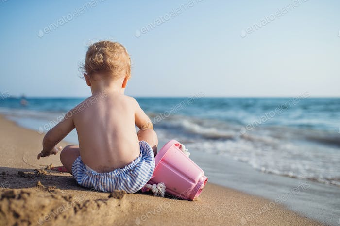 A rear view of small toddler girl sitting on beach on summer holiday, playing.