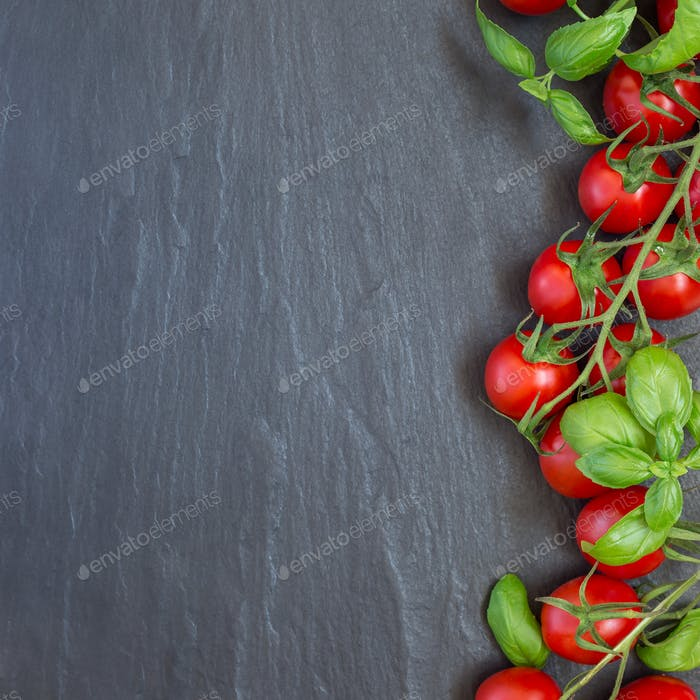 Cherry tomatoes with basil leaves on a dark slate background, to