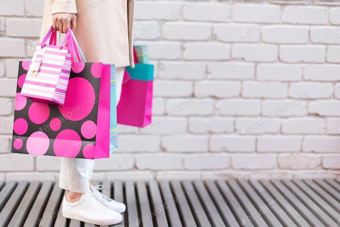Stilvolles Mädchen in weißer Kleidung hält rosa Einkaufstaschen. Sale, rabatt, black friday concept