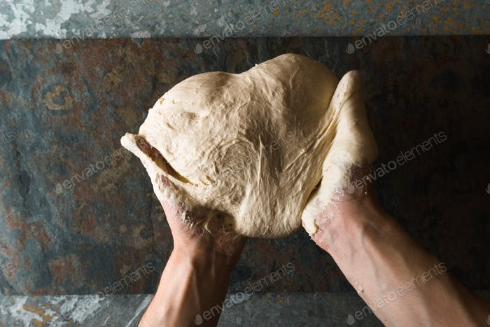 Hands with heart shaped dough top view