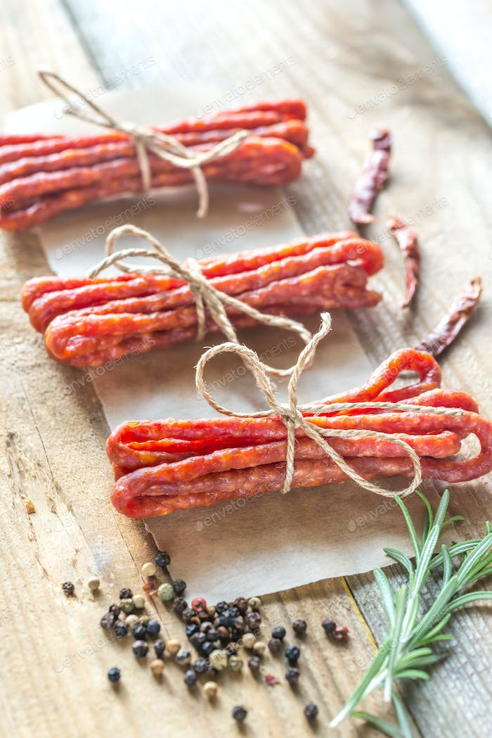 Kabanosy sausages with spices on the wooden background