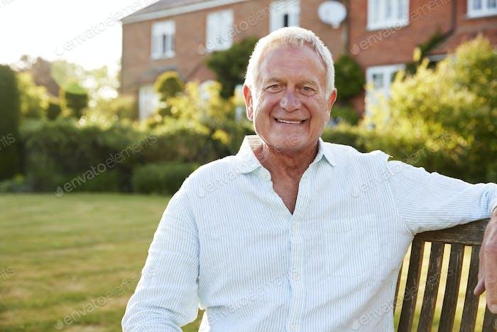 Senior Man Sitting On Garden Bench In Evening Sunlight