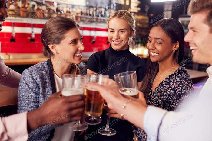 Male And Female Friends Making A Toast As They Meet For Drinks And Socializing In Bar After Work