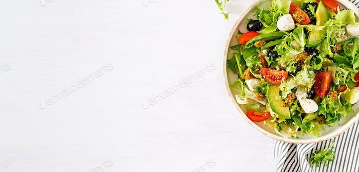 Fresh salad with avocado, tomato, olives and mozzarella  in a  bowl