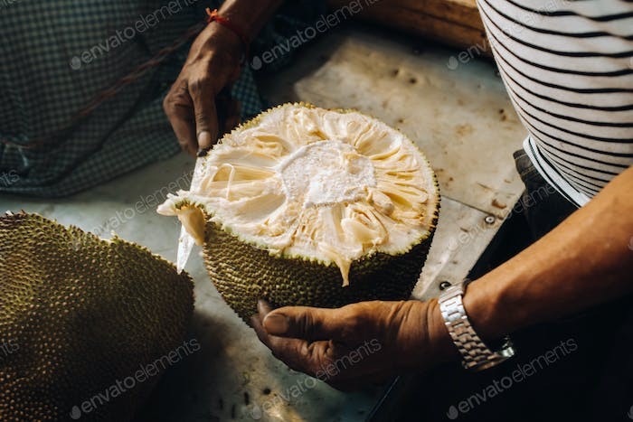 The seller cuts a juicy, ripe jackfruit for tourists. The urban market of Port Louis, Mauritius