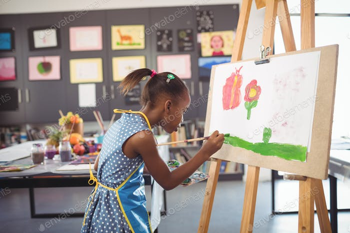 Side view of concentrated girl painting on canvas