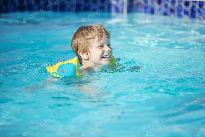 Happy blonde boy wearing floaties and swimming in pool