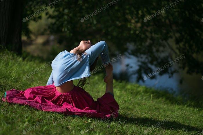 Schöne junge Frau in roten Rock üben Yoga Asana in der Natur