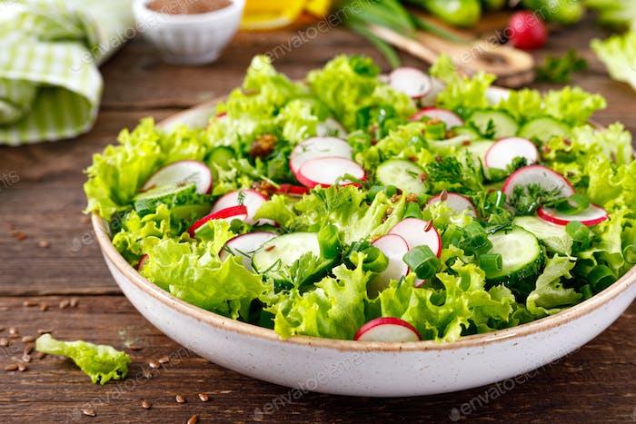 Fresh vegan vegetable salad of radish, cucumbers, lettuce, dill and green onion