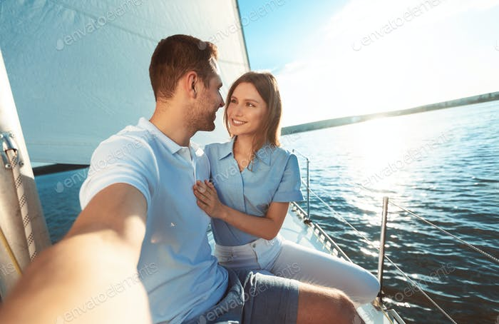 Couple Making Selfie Sitting On Yacht Deck Outdoors