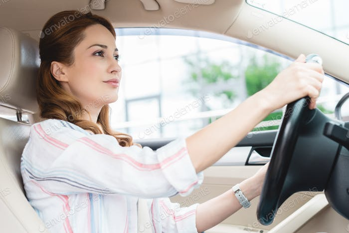 side view of attractive woman driving car alone