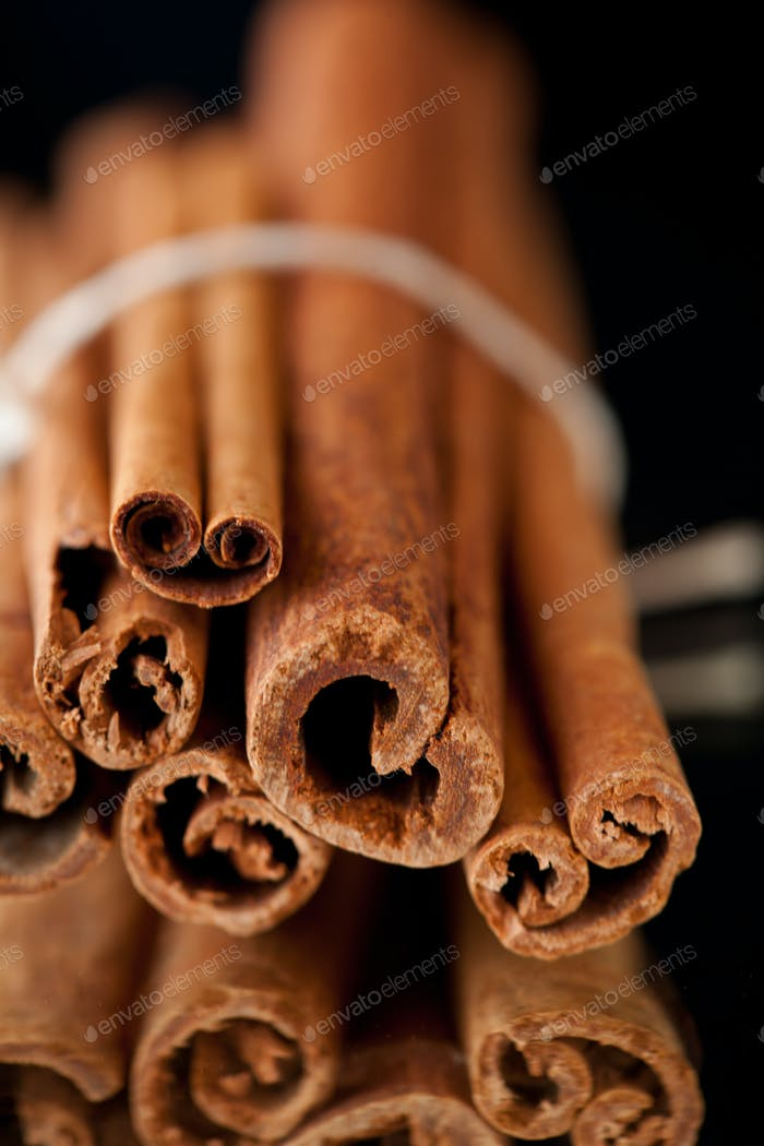Close up of cinnamon sticks against a black background