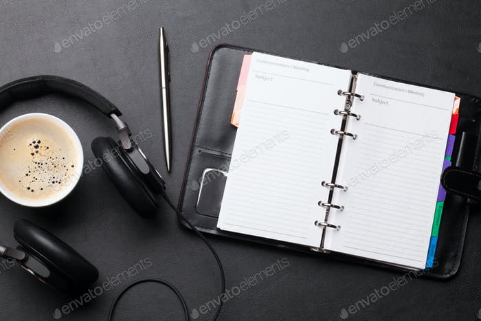 Office desk with notepad, coffee cup and headphones
