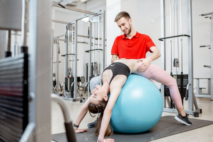 Woman exercising on a fitness ball at the rehabilitation gym
