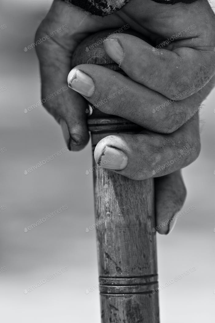 Old hand holding a stick close up