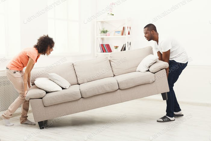 African-american couple placing sofa at new home