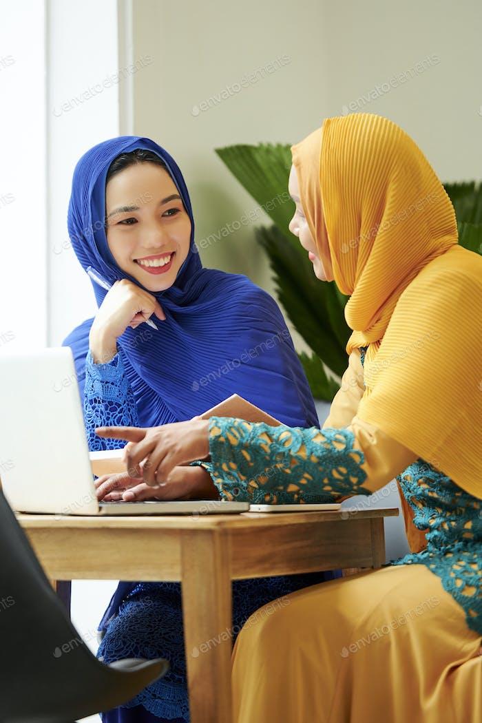 Female muslim student discussing homework